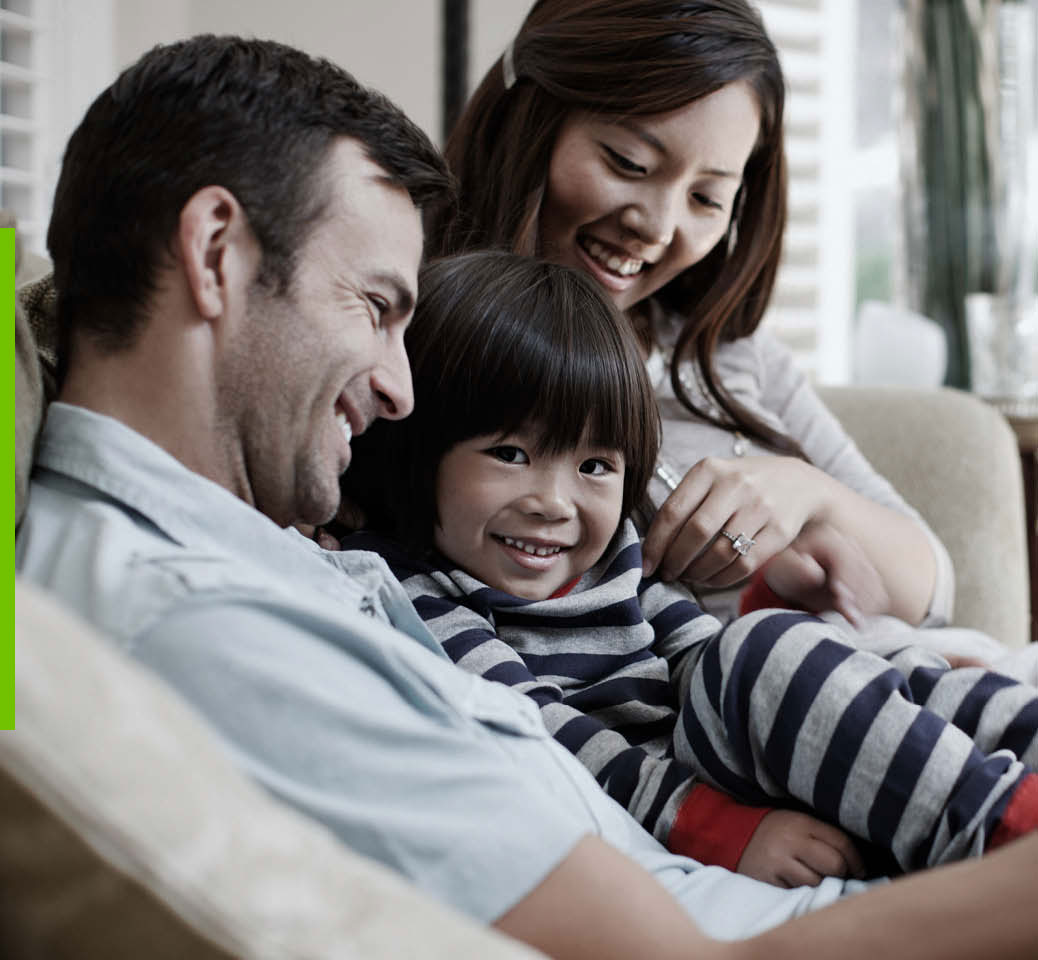 A man, a woman, and a child sitting on a couch and smiling